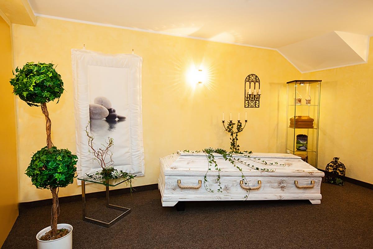 weisser holzsarg in gelbem bestattungsraum von keuser bestattungen